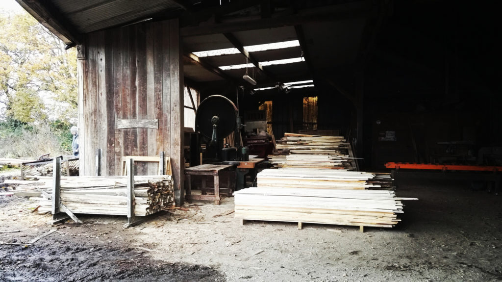 French sawmill with woodworking machines and stacked wood