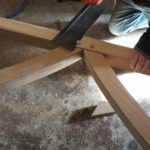 Sawing oak pegs flush with bespoke table base